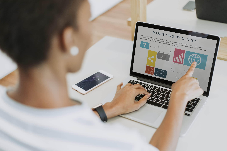 Dame travaillant sur un ordinateur portable dans son bureau sur la stratégie marketing.